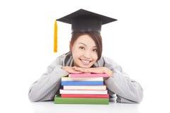 倾斜在被堆积的书的亚裔微笑的学生 免版税库存照片