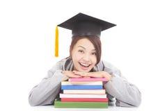 倾斜在被堆积的书的愉快的学生画象 免版税库存照片