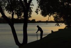 倾斜在走的藤茎的一个年长男性的剪影注视横跨湖 免版税图库摄影