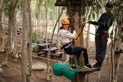 倾斜在邮编线的愉快的妇女,当站立在木平台的人拿着绳索时 库存图片