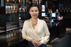 倾斜在酒吧柜台的微笑的女实业家 免版税库存图片