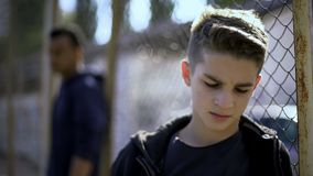 倾斜在金属的生气青少年的男孩操刀,放弃与社会,孤儿院 库存图片