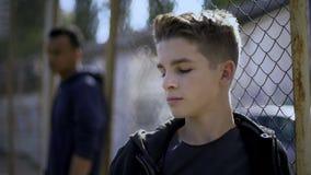 倾斜在金属篱芭,少年拘留中心,孤儿院的十几岁的男孩 免版税库存照片