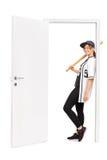 倾斜在门的女性棒球运动员 免版税库存照片