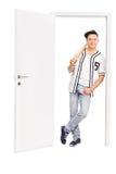 倾斜在门的年轻棒球运动员 图库摄影