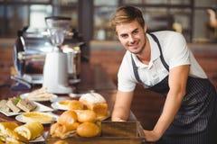 倾斜在食物桌的英俊的侍者 免版税图库摄影
