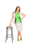 倾斜在高凳子的女商人立场 免版税库存照片