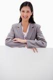 倾斜在死墙的微笑的年轻女实业家 免版税库存图片