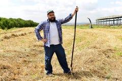 倾斜在他的叉子的严肃的农夫在坚苦工作天以后 免版税库存照片