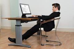 倾斜在他的椅子的商人,当工作在计算机时 免版税库存图片