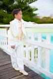 倾斜在a的白色木篱芭的年轻人第一个圣餐男孩 库存照片