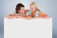 倾斜在whiteboard的逗人喜爱的愉快的夫妇的综合图象 库存照片