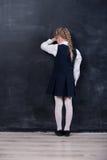 倾斜她的前额的女小学生反对黑板 库存图片