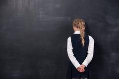 倾斜她的前额的女小学生反对黑板 免版税库存照片