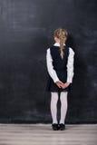 倾斜她的前额的女小学生反对黑板 图库摄影