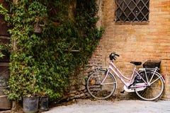 倾斜对一个小托斯坎镇的墙壁的自行车 库存照片