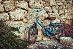 倾斜对一个石墙的老蓝色葡萄酒自行车在阳光下在地中海 库存图片