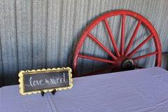 倾斜对一个谷仓的墙壁的马车车轮有标志的在一次传统古板的婚姻的庆祝的一张桌 库存图片