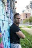 倾斜对五颜六色的街道画墙壁的英俊的肌肉人 免版税库存照片