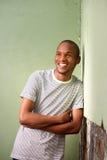 倾斜对墙壁和微笑的年轻美国黑人的人 免版税库存照片