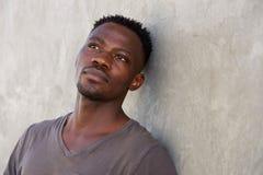 倾斜对墙壁的体贴的年轻非洲人 免版税库存图片