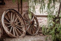 倾斜对墙壁的老打破的马车车轮 免版税图库摄影