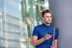 倾斜对墙壁的英俊的年轻人外面与手机 免版税库存图片