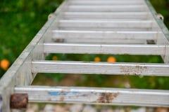 倾斜对房子的墙壁的一架长的银色铝梯子的顶视图 关闭从高梯凳上面的看法  免版税库存照片