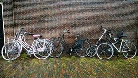 倾斜对房子的砖墙的美丽的现代时尚自行车的大数在城市街道 免版税图库摄影