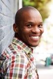 倾斜对灰色墙壁和微笑的愉快的年轻黑人 库存图片