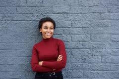 倾斜对灰色墙壁的可爱的微笑的非洲妇女 免版税库存照片