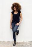 倾斜对白色墙壁的微笑的年轻非洲妇女 免版税图库摄影