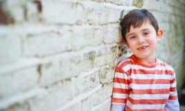 倾斜对砖墙的逗人喜爱的愉快的男孩 图库摄影
