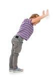 倾斜对空白墙壁的小女孩。 库存图片