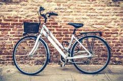 倾斜对红砖墙壁的自行车 库存照片