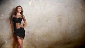倾斜对老墙壁的透明鞋带黑色礼服的迷人的年轻深色的妇女。在老墙壁附近的性感的华美的少妇 免版税库存照片