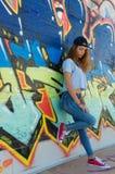 倾斜对街道画墙壁的哀伤的少年 免版税图库摄影
