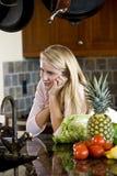 倾斜少年认为的逆女孩厨房 图库摄影
