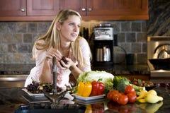 倾斜少年认为的逆女孩厨房 免版税库存照片