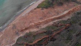 倾斜山崩缺点空中射击在海海岸线附近的在多云天气 股票录像