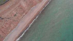倾斜山崩缺点空中射击在海海岸线附近的在多云天气 股票视频