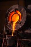 倾斜熔炉的钢铁工人在一个工业铸造厂 库存图片