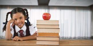 倾斜由书和苹果的女小学生的综合图象在书桌 免版税库存图片