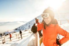 倾斜的少妇滑雪者 微笑在滑雪设备、佩带的风镜和盔甲的少妇画象 库存照片