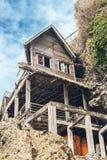 倾斜的木房子在海滩晴天 免版税库存图片