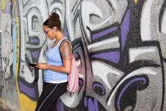 倾斜的被刺字的女孩在街道画墙壁 免版税库存照片