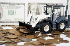 倾斜硬币的拖拉机 财务 免版税图库摄影