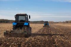 倾斜领域 两大蓝色traktor犁在收获玉米庄稼以后犁了土地 免版税图库摄影