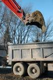 倾销红色垂直的挖掘机的土 免版税库存照片