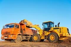 倾销者挖掘机装入程序卸车轮子 图库摄影